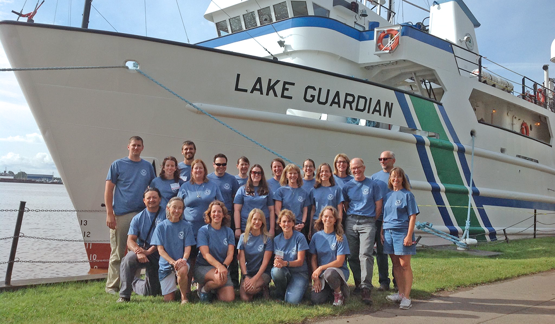 group of people pose in front of a large boat called the Research Vessel Lake Guardian