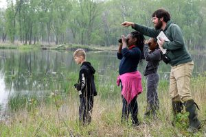 Students use binoculars to watch birds