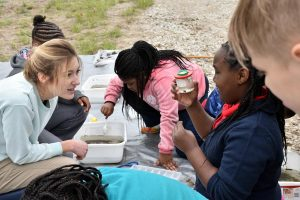 Student looks at invertebrate in water