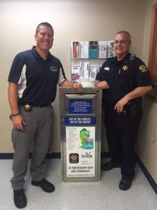 Two police officers stand next to a medicine collection box with IISG branding
