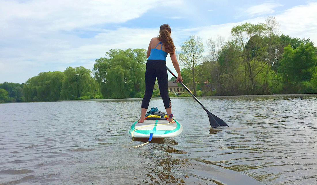 Woman stand-up paddle boarding on the Sheboygan River