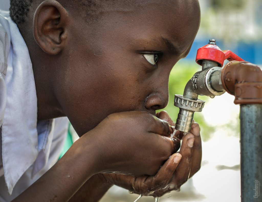 Child drinks from water hose