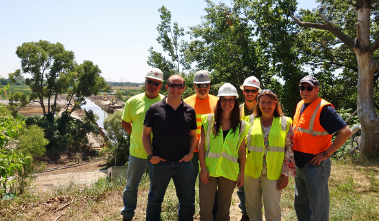 Zephyr project partners stand in construction gear in front of the remediation site