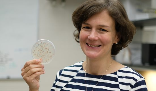 woman holds up a petri dish with visible microbes present