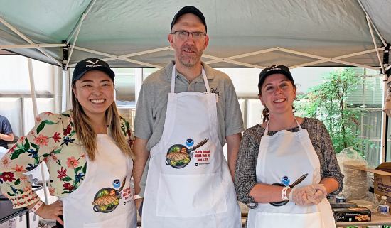two women and a man stand under a tent wearing Illinois-Indiana Sea Grant hats and white NOAA Fish Fry aprons