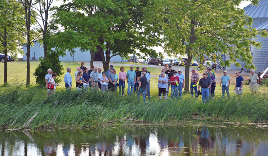 people stand at edge of pond while a man speaks to them using a microphone