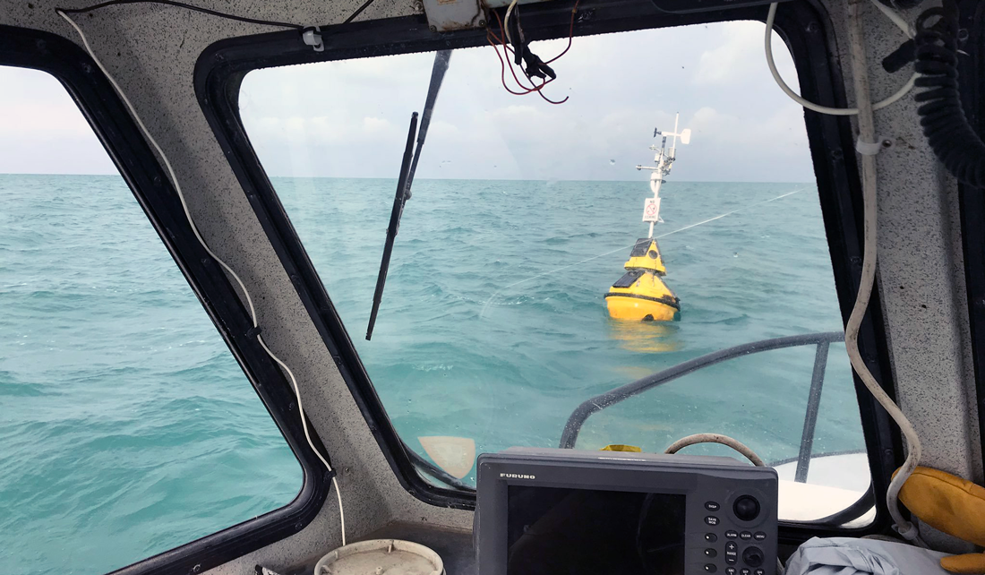 floating yellow buoy can be seen in water through a boat window