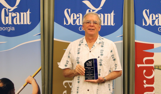 Brian Miller holds the William Q. Wick Award from the Sea Grant Extension Assembly