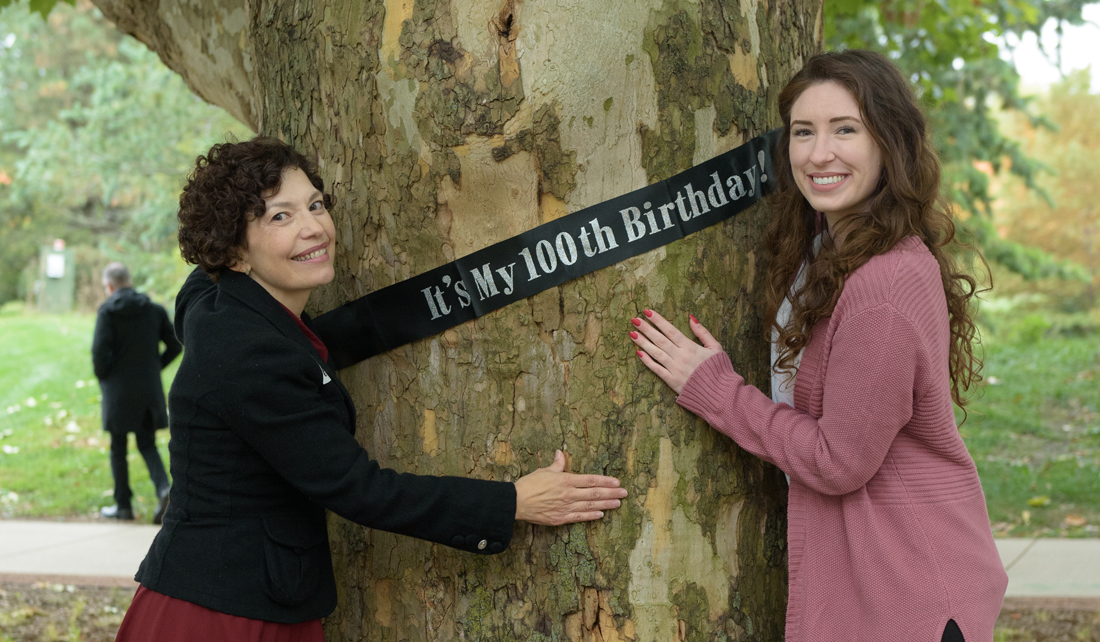 "two women hug a tree with a banner that reads ""it's my 100th birthday!"""