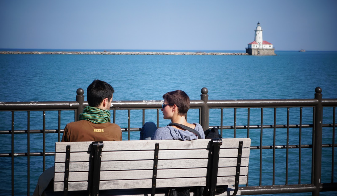 two young people sitting on a bench at the edge of Lake Michigan, with a lighthouse in the background