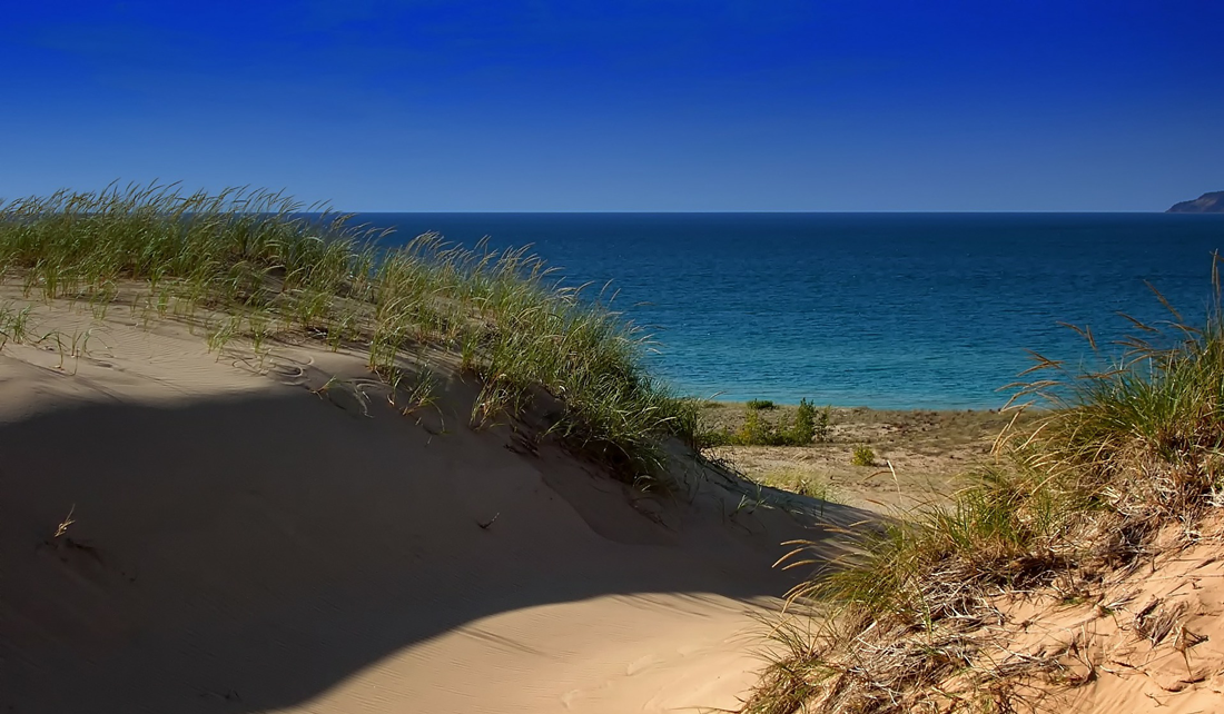 sand dunes and grass in the forefront, water of Lake Michigan in the background beyond the dunes