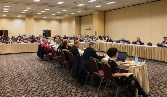 people sitting at tables in a large conference room