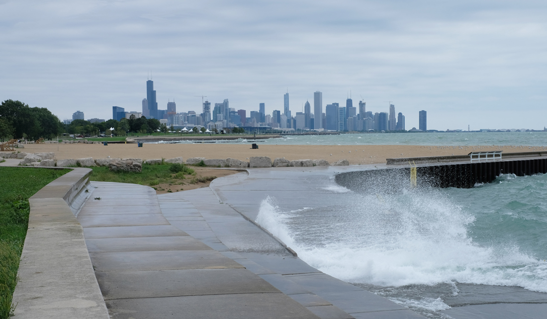 waves crashing over constructed shoreline with Chicago skyline in the background