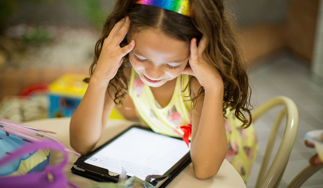 Young girl sits at a table and smiles down at an electronic tablet, backpack sitting beside her