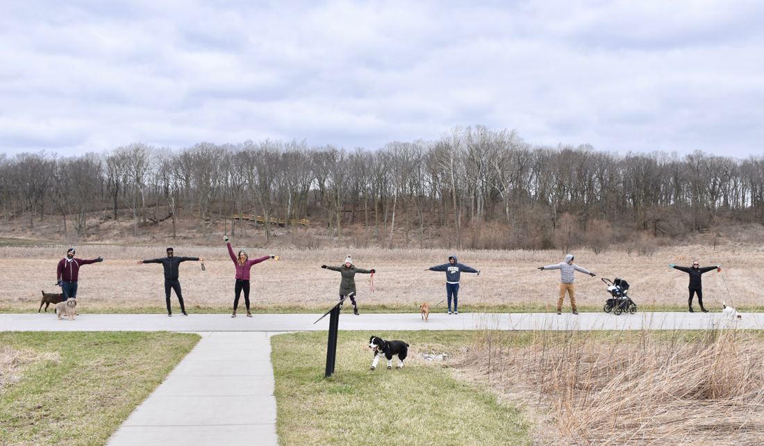 several people stand on a park path with their arms out, at least 6 feet apart from the next person