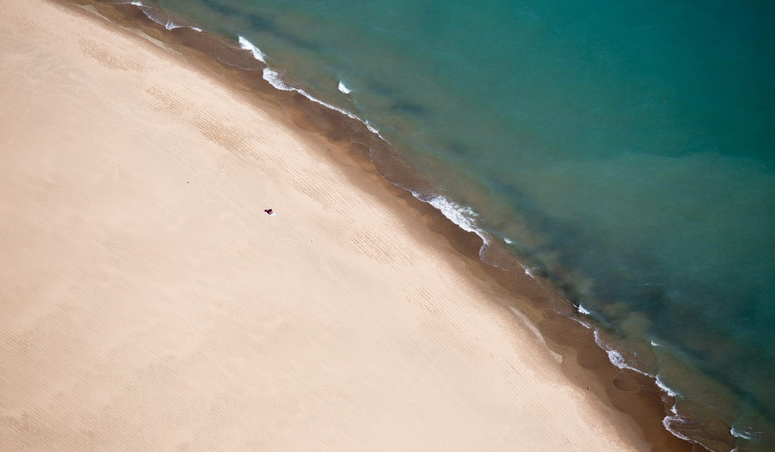 aerial of beach and shoreline with one tiny person visible