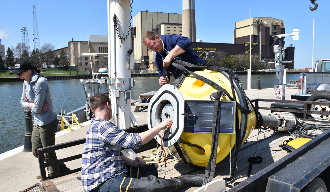Two people work on a large, yellow buoy on the back of a trailer parked next to Lake Michigan