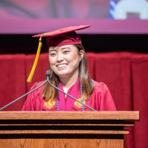 woman in red cap and gown at podium, speaking into microphone