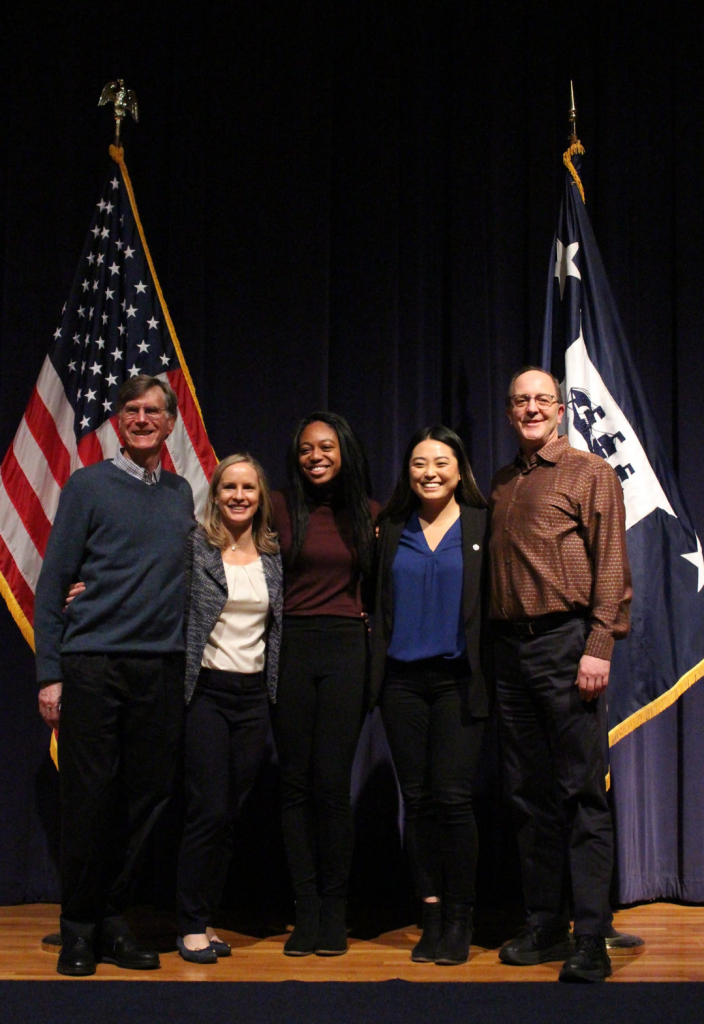 group of people stand on a stage posing for a photo next to the American flag