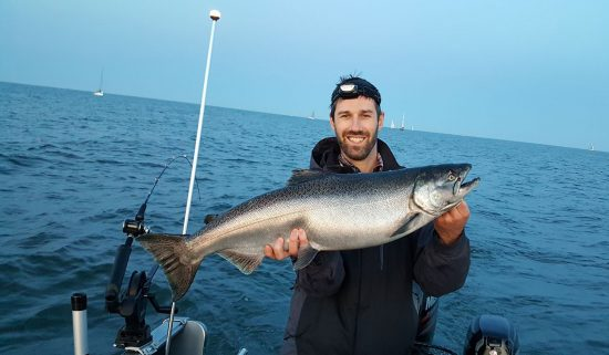 Man on a boat holding a Chinook salmon